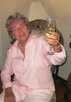 Mardie Schroeder, holding a glass of white wine